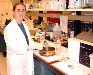 Susan Heyel in a lab in front of equipment.